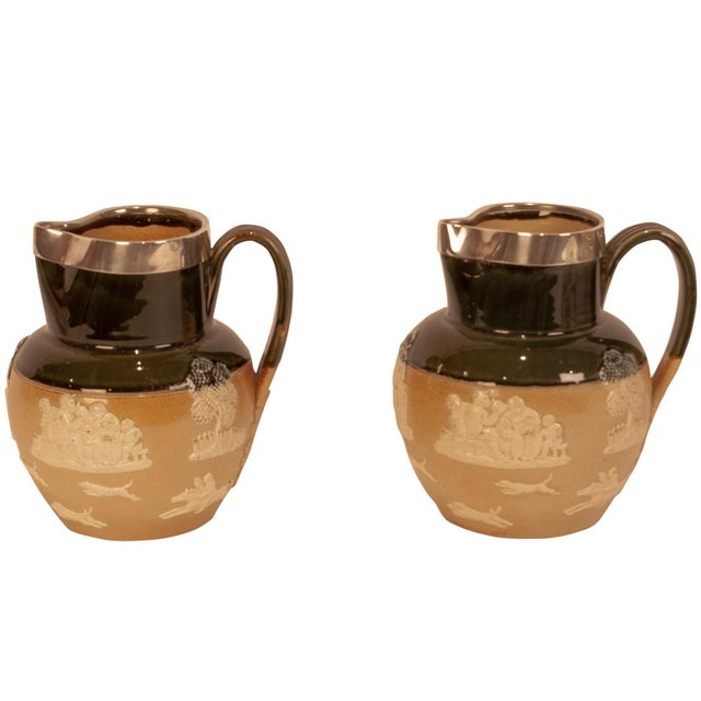 A pair of Royal Doulton pottery pitchers with silver rims, English hallmark date 1900