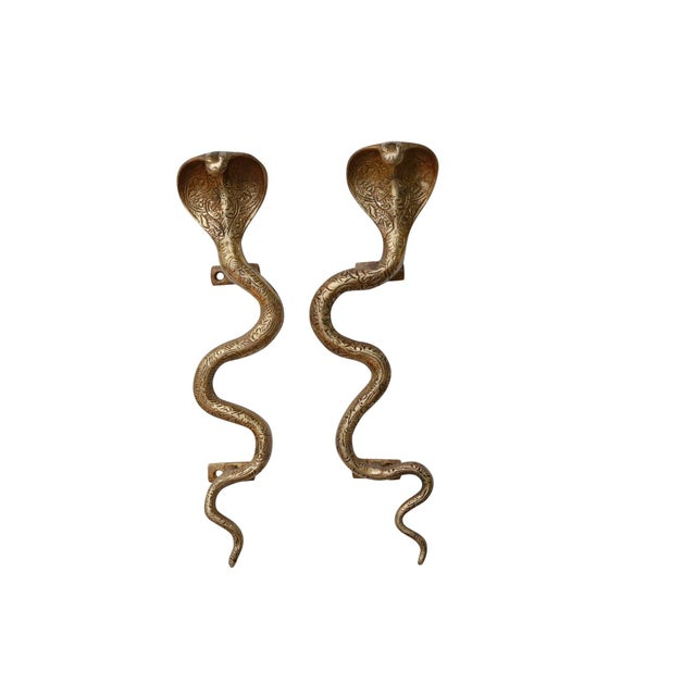 A pair of large golden brass cobra door handles or cabinet pulls. Hollywood Regency in style, with intricate carving...