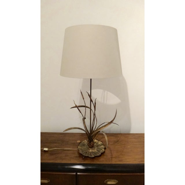 A sculptural and delicate gilt metal cattail reed design tall table lamp with a modern, linen-like light tan fabric shade....