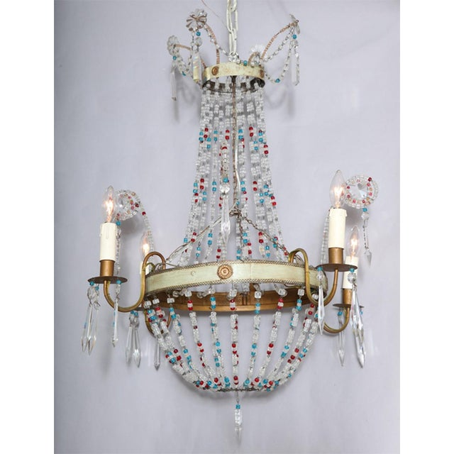 Chandelier in classic European Empire shape with a twist; two painted tole rings with gilt rosettes accent suspended by...