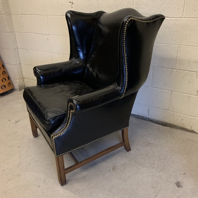 Beautiful vintage shiny black leather wing back chair in excellent condition. Classic Chippendale wing back style with...