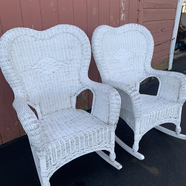 Pictured here is a beautiful pair of white wicker antique rocking chairs, a wonderful addition for a covered porch or...