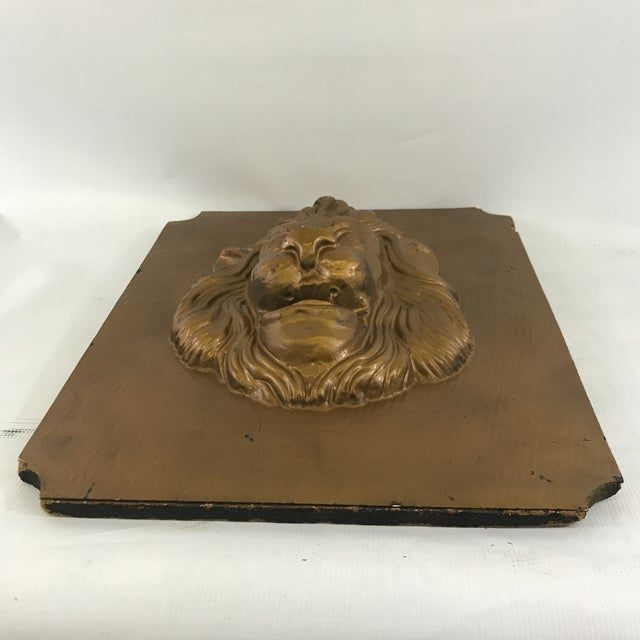 Vintage plastic lion sculpture mounted on composite board with gold painted finish.