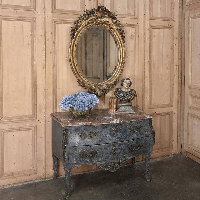 19th Century French Louis XVI Gilded Oval Mirror is poised to create a lavish decorative touch to any room, with its...