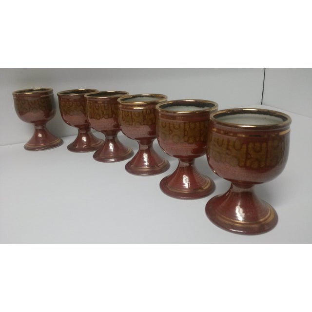 This is a set of 6 artisan pottery wine goblets. The work on these goblets is stunning. They are a deep rust with gold...
