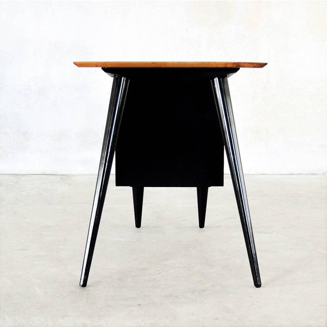 Two-tone solid maple and black lacquered desk supported by drawers on one side and the signature angular tapered legs on...
