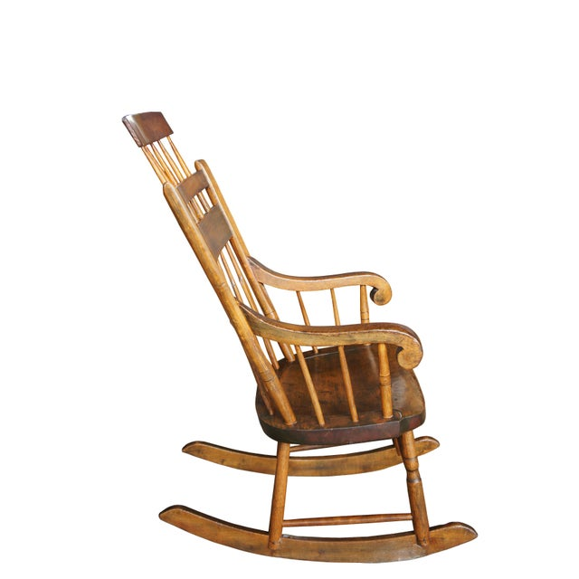19th century Windsor rocking chair. Made from Chestnut. Features scrolled arms over spindles leading down from a spindled...