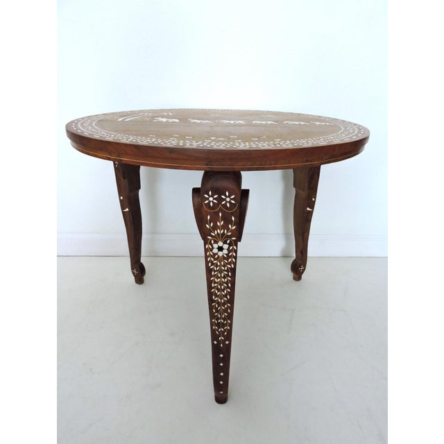 An intricately hand crafted solid teak occasional table, round top, painstakingly inlayed with fine brass wires, bone and...