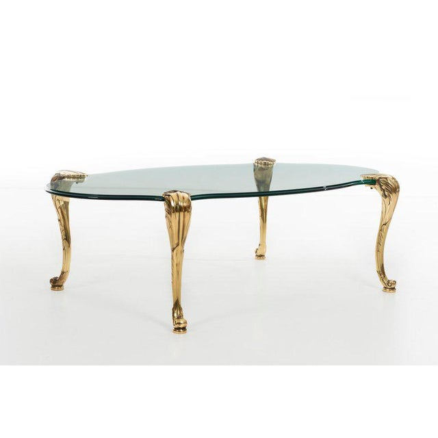 Chapman Low stepped glass coffee table raised on four sculptural, stylized cabriol legs in patinated brass.. Executed by...