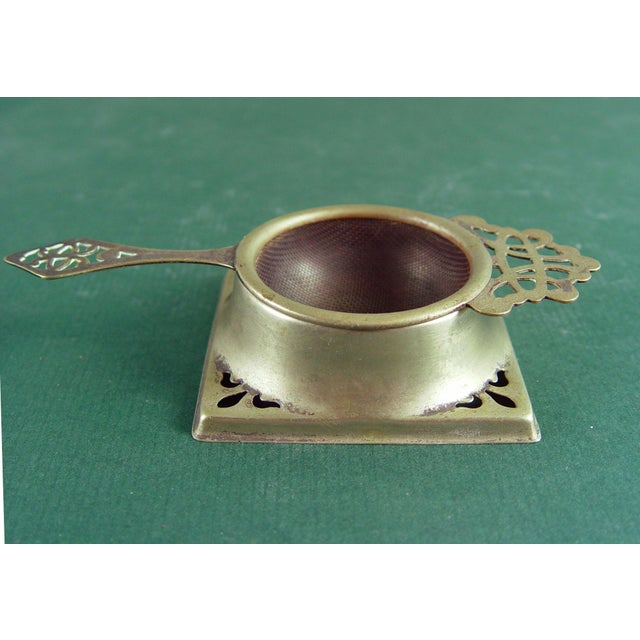 Circa 1910 tea strainer with stand. Silver over nickel with pierced work. Marked EPNS Made in England on back. Straining...