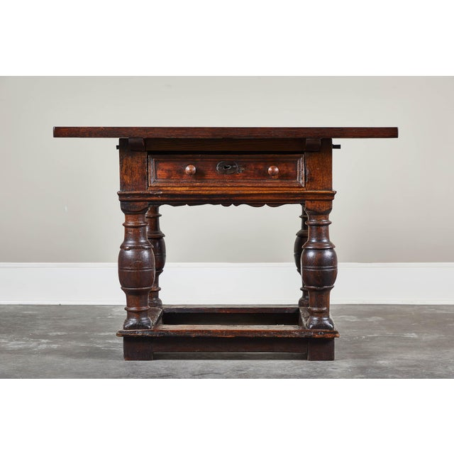 An 18th century Danish baroque style table featuring one drawer with two handles and interesting turned legs. The table...