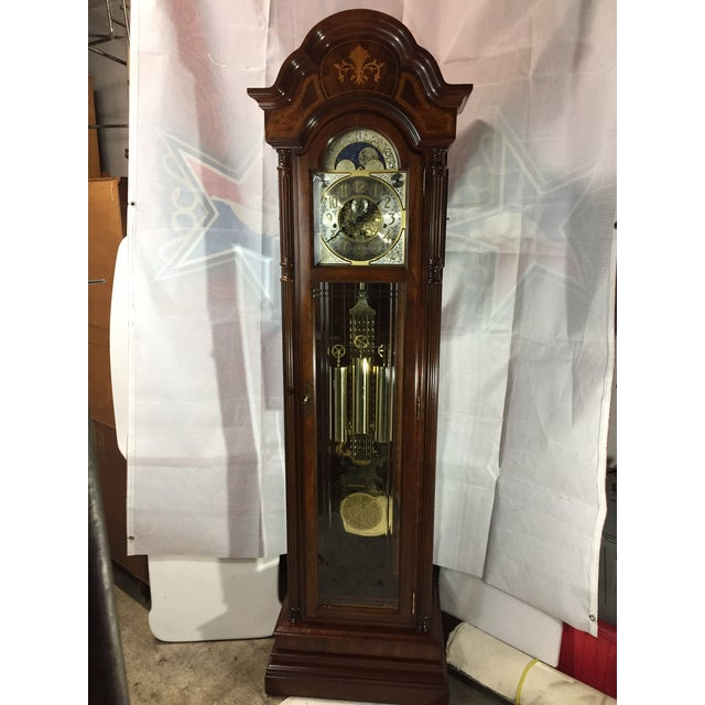 Traditional Walnut wood case, leaded glass on three sides, three brass weights and ornate pendulum. Clock face has...