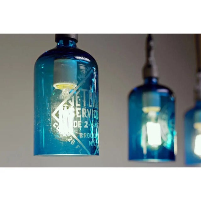 Etched glass seltzer water bottles have been transformed into hanging pendant lights, either hard-wired or plug-in...