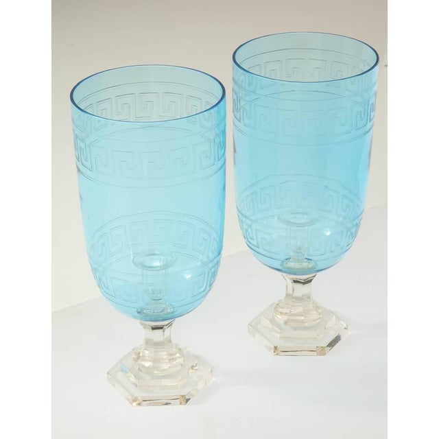 A pair of glass hurricane candleholders in a stunning blue with an etched Greek key design on a clear glass pedestal....