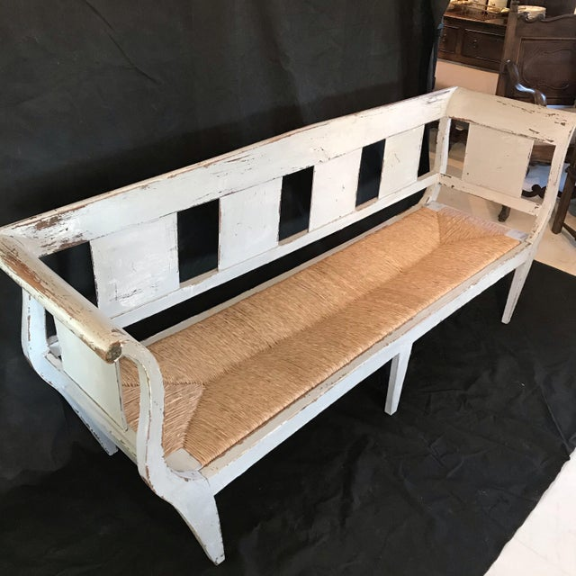 A wonderful long distressed painted grey bench having curved arms, slatted back, gold rosettes on armrest ends, and...