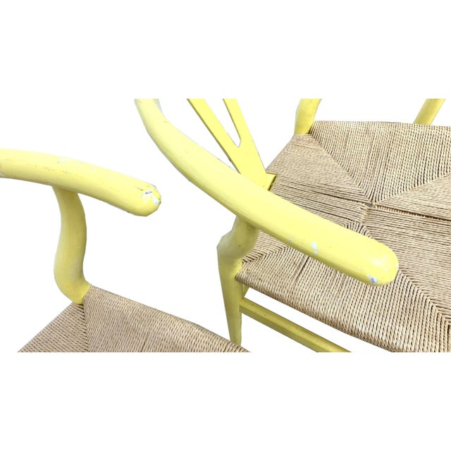 These wishbone chairs are painted in a wonderful yellow with rush seats. In 1944, Danish designer Hans Wegner began a...