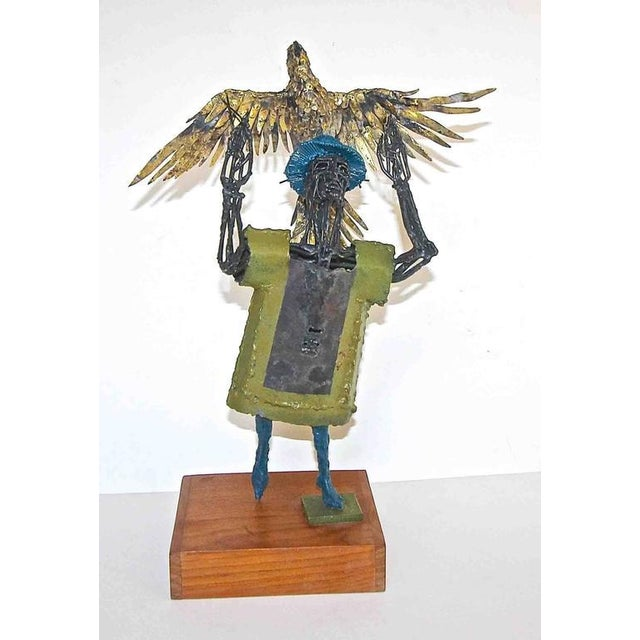 Original metal sculpture of man holding eagle mounted on wood base by renown Texas artist and sculptor, Bob Fowler...