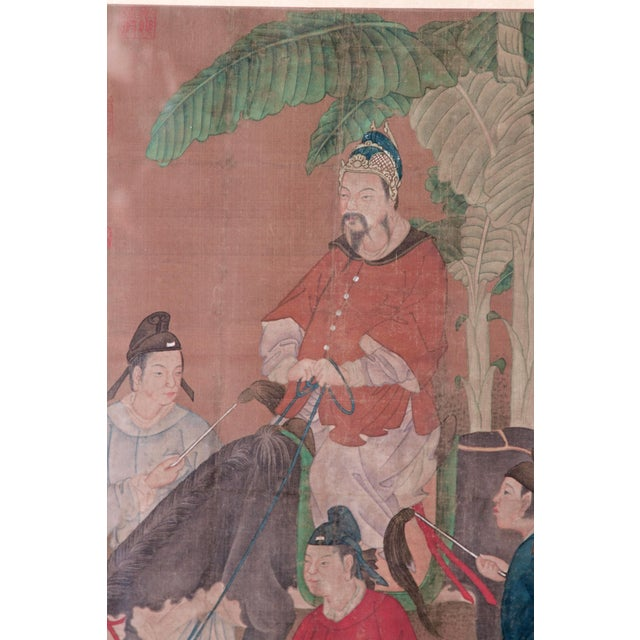 A Chinese scroll painting of a dignitary on his horse with three attendants in a treed landscape. Black and gilt modern...