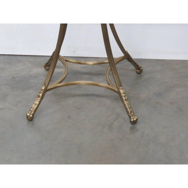 Hollywood Regency style glass top gueridon with feathered feet.