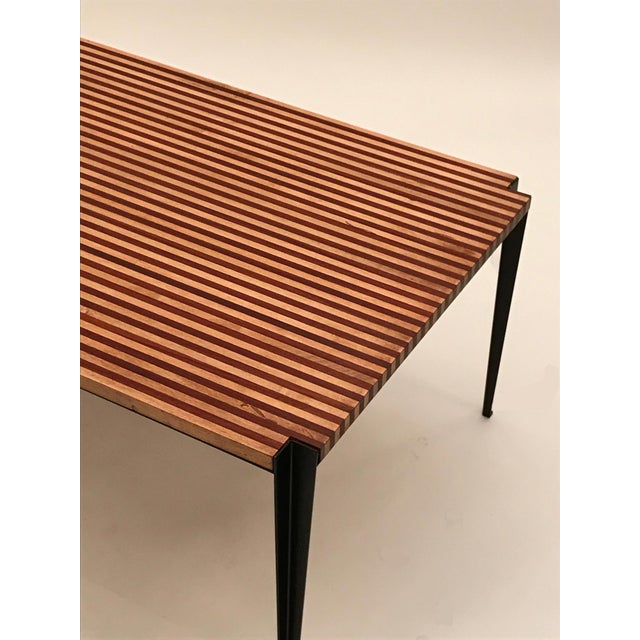 pair of large scale cocktail tables each featuring frames in blackened steel with inverted angled tapering legs. The...