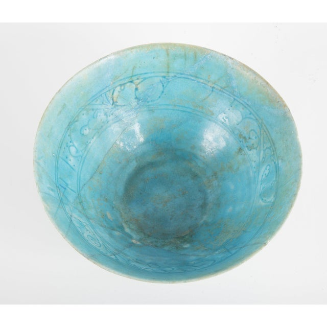 Footed conical form Kashan turquoise glazed pottery bowl. Interior incised with foliate band.