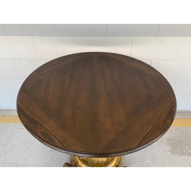 """Antique English brass and mahogany lion motif pub table, with circular 35.5"""" diameter mahogany top, on a tripod brass base..."""