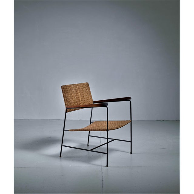 A Mid-Century armchair by Arden Riddle, made of a wrought iron frame with a woven rattan seating and backrest. The rounded...