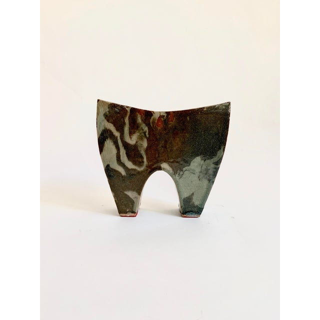Vintage studio ceramic vase with a deep, glossy glaze and nearly camouflage pattern to it. There is a digital/printed...