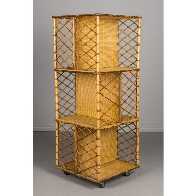A Mid-Century Modern French rotating or swivel bookcase on wheels, with a sturdy bamboo frame and tightly woven rattan...