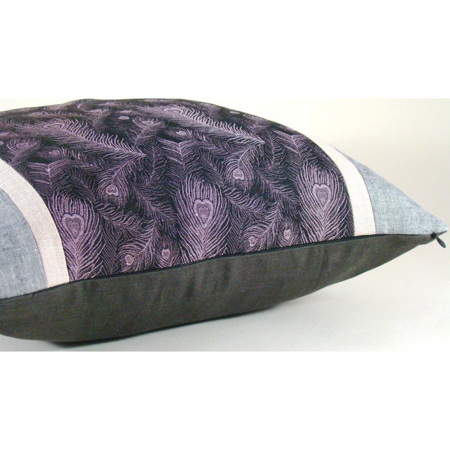 Lavender peacock feathers are scattered against a black ground in this limited edition pillow cover fashioned from a...