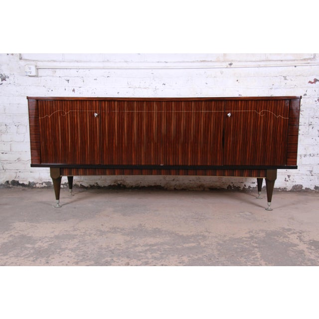 An outstanding French Art Deco sideboard, credenza, or bar cabinet by N.F. Ameublement. The sideboard features stunning...