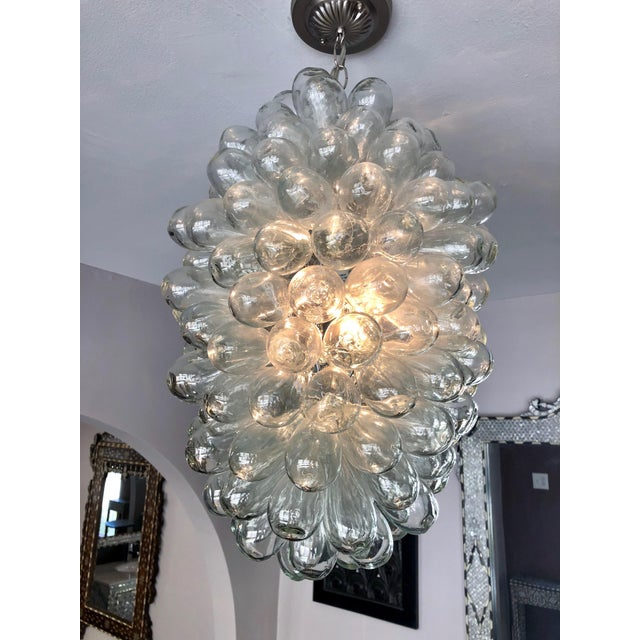 This sculptural light fixture is composed of clear individual handblown balloon shaped pieces, individually attached to a...
