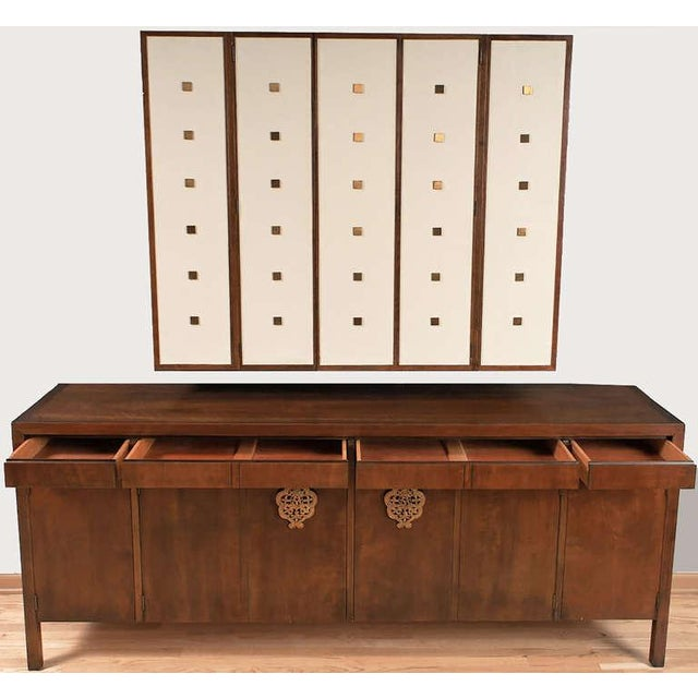 By Bert England for Johnson Furniture, this long walnut sideboard cabinet has flush drawers over doors adorned with large...