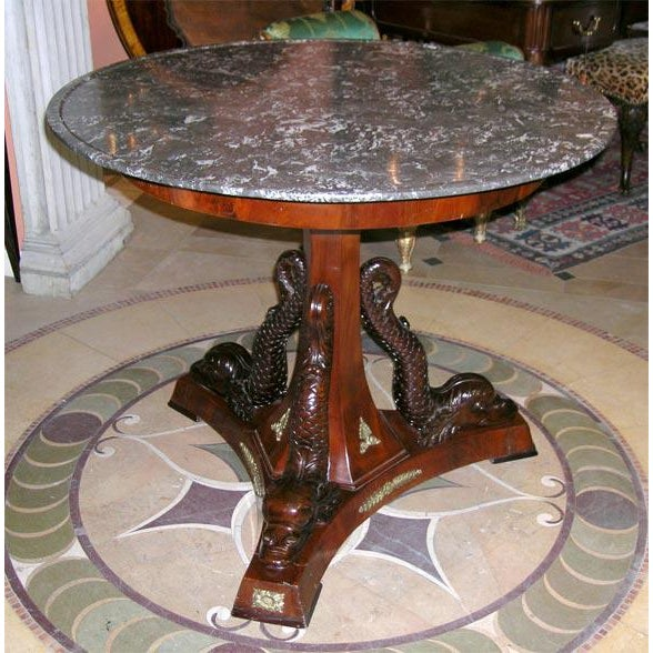 Fine French Empire marble-top bronze mounted center table with beautifully carved Dolphins on Tripartite Base. The dish...