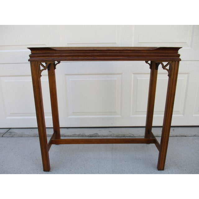 This vintage Chippendale style console table has a banded top surrounded by a gorgeous curved upper lip. The wood grain on...