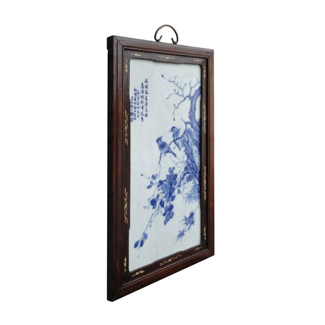 This is a Chinese porcelain painting which has tree, birds and Chinese poems in blue and white color. The wood frame is...