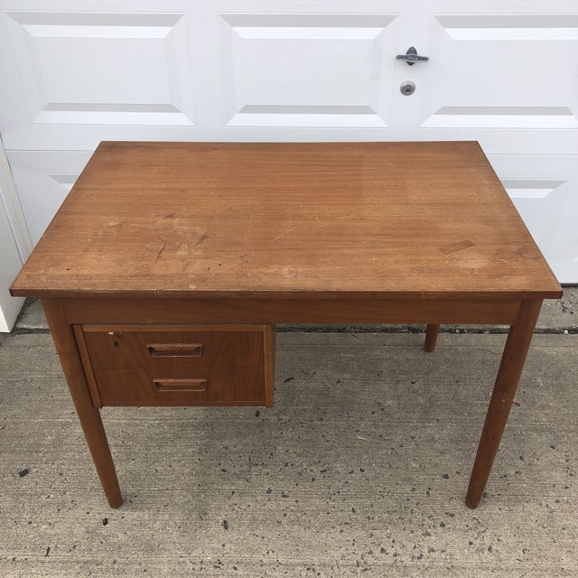 This vintage writing desk features solid wood construction, teak finish, and two adjustable drawers that can be moved from...