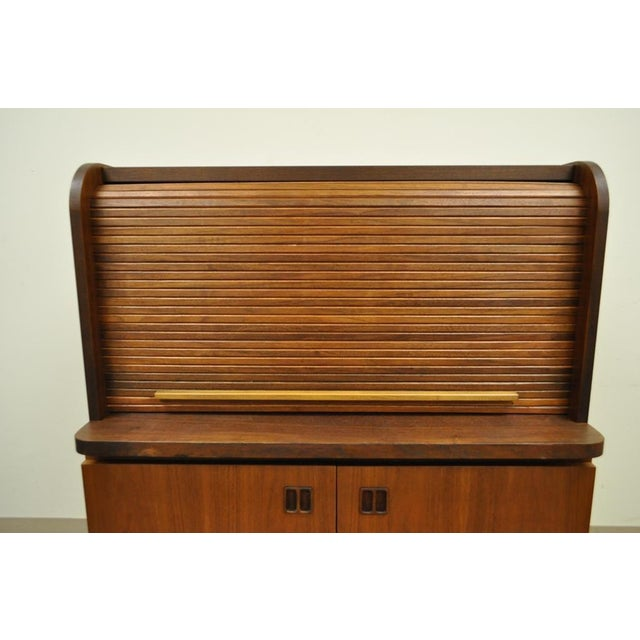 Item: Striking Vintage Mid Century Modern Teak Roll Top Secretary Desk. The desk features a tambour roll top with pull out...