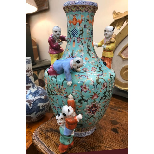 A turquoise ground Chinese famille rose vase with five boys. Vase decorated with scrolls and florals.