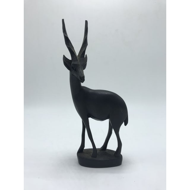 This Dark Brown Wood Antelope Sculpture is an adorable accent piece. It would like great in a mid-century style home!...