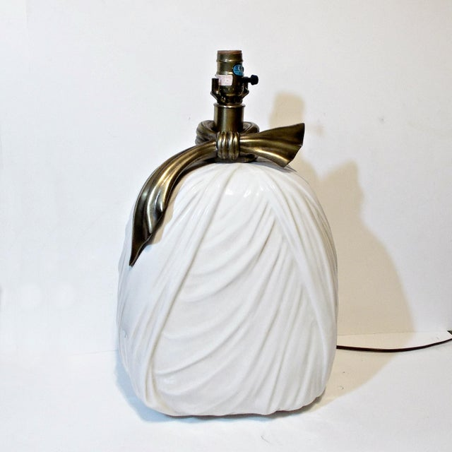 This is a 1980s Hollywood Regency style Chapman lamp. The base is white porcelain made to look like draped fabric and the...