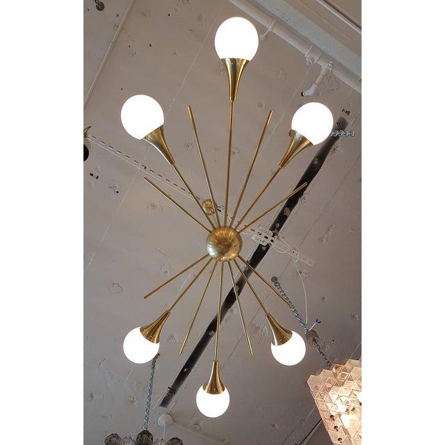Mid-Century Modern Italian, Stilnovo style, six-arm brass and six white glass globes Sputnik chandelier. Made of a brass...