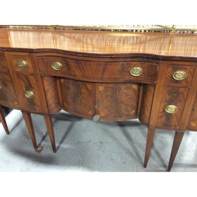 1940 sideboard in the Hepplewhite style of 1800. Serpentine with great form this is made of mahogany, mahogany veneers,...