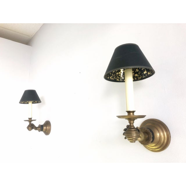 A true pair of brass sconces, a graceful hand holding the light source. Retain vintage black shades. In working order.