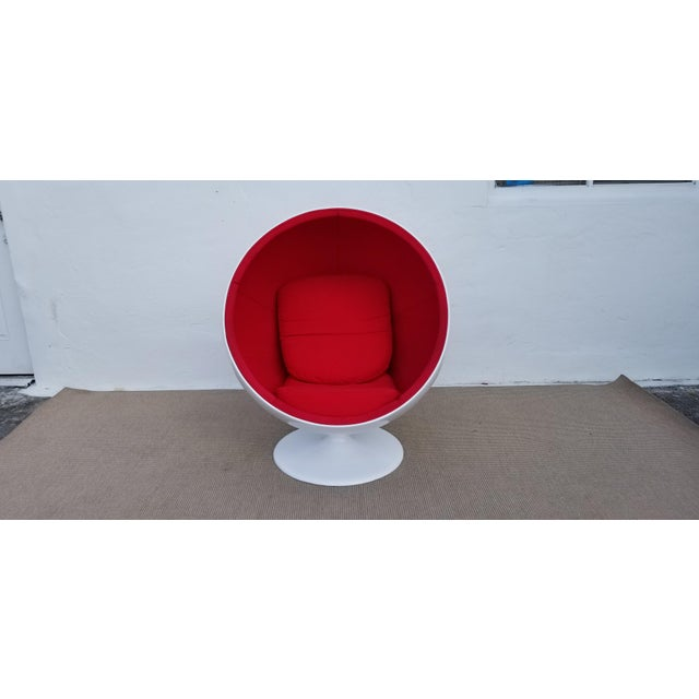 Eero Aarnio style white painted fiberglass body with red upholstery. Chair is in excellent vintage condition the fabric is...