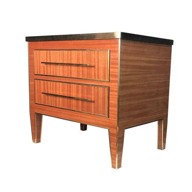 Two drawer nightstand completed in mahogany veneer and hand formed brass detailing. Slim bronze puller completes the...