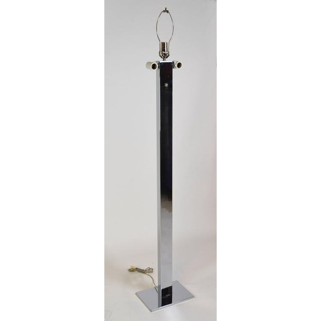 A high quality stainless steel floor lamp. A rectangular shaft sits on a flat slab. With two ceramic double Edison sockets...