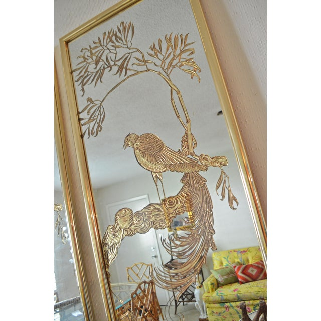 Vintage Hollywood Regency style mirrors. Shiny brass frames hold mirrors with stunning gold bird etchings. Incredible...