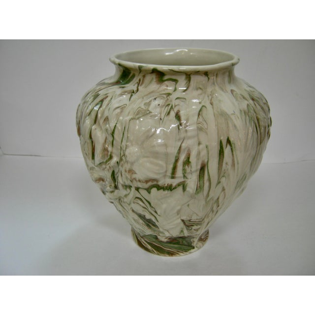 Gorgeous glazed floral relief mottled vase embellished with greens, browns against a cream background. This vase came from...