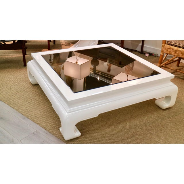 Gorgeous newly white lacquered Chinese coffee table with smoked glass. Dimensions: 46 - 46w - 14.5h